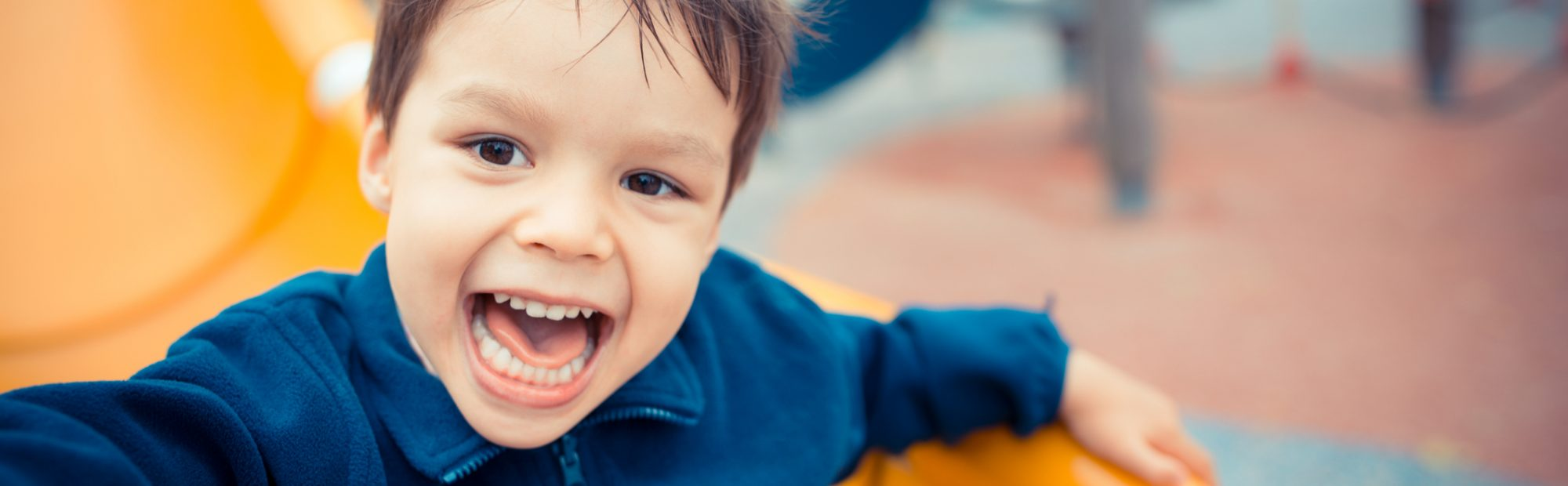 Cute little boy playing on slide